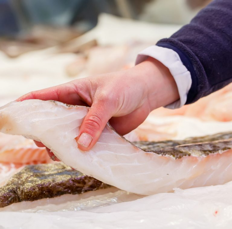 Fishmonger holding a piece of fresh fish in a market